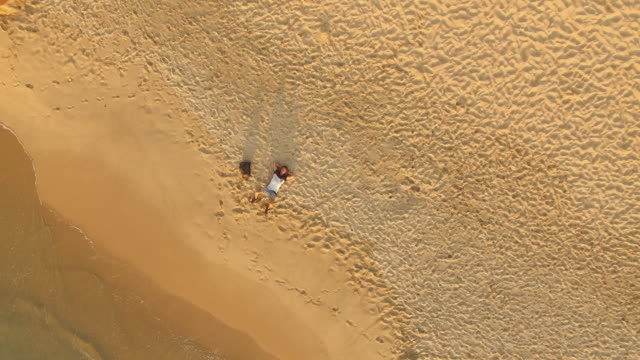 aerial view of young man lying in the sand of beautiful beach at sunset - liegen stock-videos und b-roll-filmmaterial