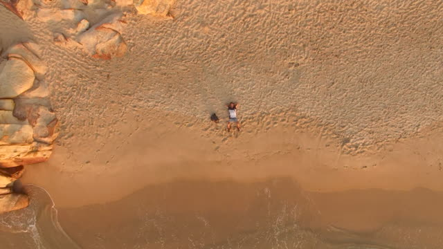vidéos et rushes de aerial view of young man lying in the sand of beautiful beach at sunset - un seul homme