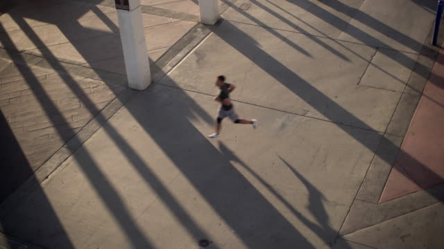 Aerial view of Young man running  across a road