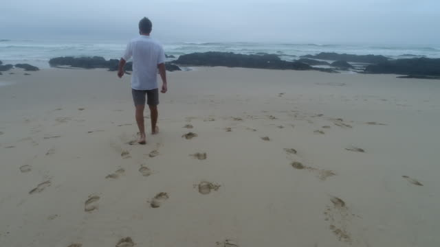 aerial view of young man walking on beach in south africa - impronta del piede video stock e b–roll