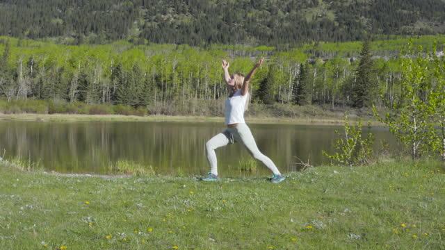 vídeos de stock, filmes e b-roll de vista aérea de jovem fazendo yoga pelo lago da montanha na primavera - braço humano