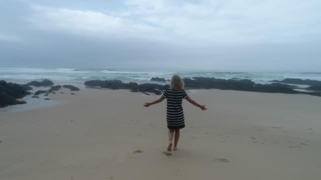 Luftaufnahme der jungen Frau zu Fuß am Strand