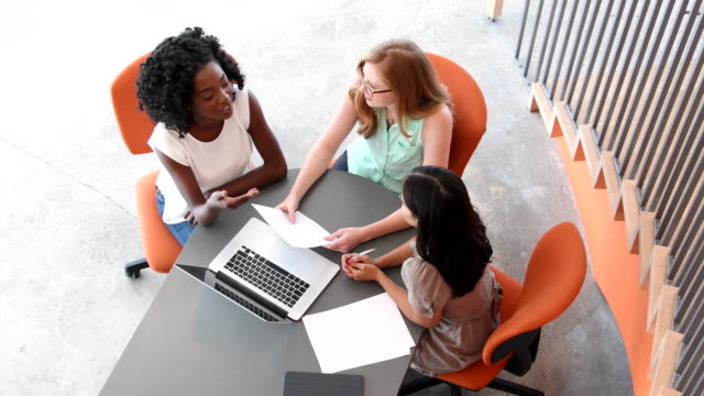 aerial view of young women in business meeting working together - casual clothing stock videos & royalty-free footage