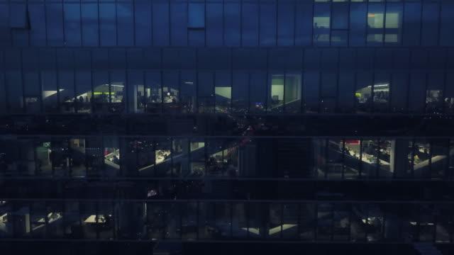 vidéos et rushes de fenêtres de bureau de vue aérienne des gratte-ciel à la nuit - image