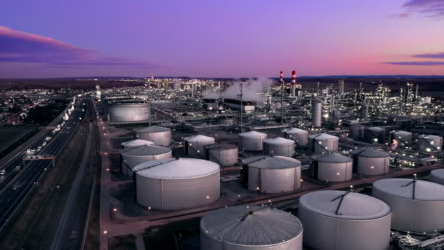 ws aerial view oil refinery and freeway at dusk - gas stock videos & royalty-free footage