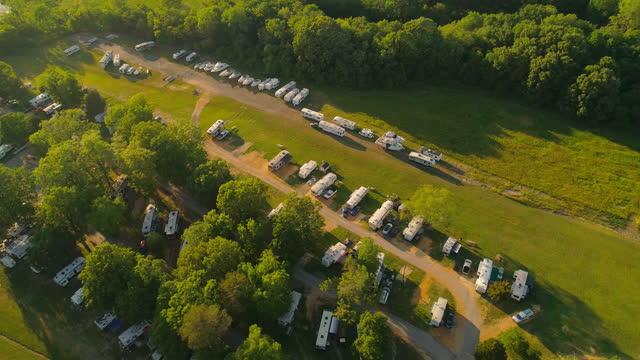 vidéos et rushes de vue aérienne sur un camp de camping-cars public - parc à roulottes dans la forêt. - parc naturel