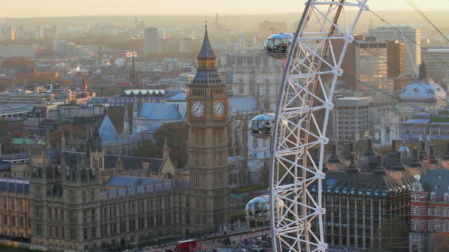 vidéos et rushes de aerial view on houses of parliament and london eye in london at sunset. - londres