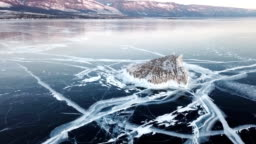 Aerial view on Lake Baikal. Winter lake with beautiful ice. Rocks on the coast and islands. Russian Winter. Drone shot.