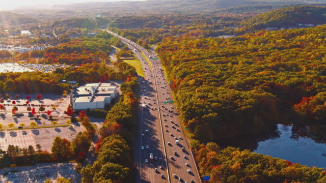 aerial view on the busy highway in mountains in new jersey, usa.  a big plaza is closed, and the parking lot is empty because of the covid-19 pandemic. aerial drone video with the panning camera motion. - new jersey stock videos & royalty-free footage