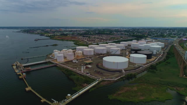 aerial view on the oil storage tanks at a petroleum terminal over the outerbridge crossing bridge, in new jersey at the border with the new york state on the arthur kill tidal strait shore. - toxic waste stock videos & royalty-free footage