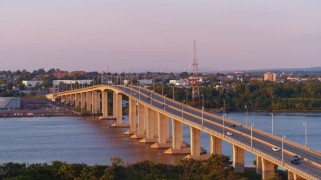 vídeos de stock e filmes b-roll de aerial view on the victory bridge over the raritan river, new jersey, in the evening before the sunset, with a remote view on manhattan, new york city, in the backdrop. video footage with the forward camera motion. - remote location