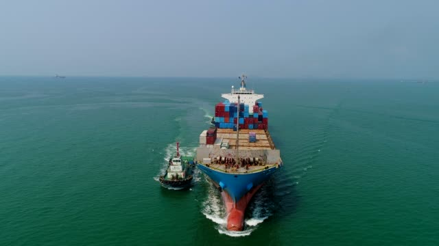 aerial view or front view tugboat drag container ship from sea port driving on the sea for logistic import export or transportation. - ship stock videos & royalty-free footage