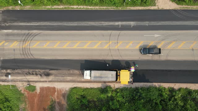 aerial view or top view on the road rollers working on the road repair by using asphalt at road construction site, 4k video - asphalt stock-videos und b-roll-filmmaterial