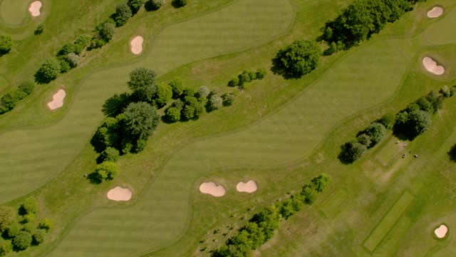 aerial view over a beautiful golf course in sunshine. 4k - golf course stock videos & royalty-free footage
