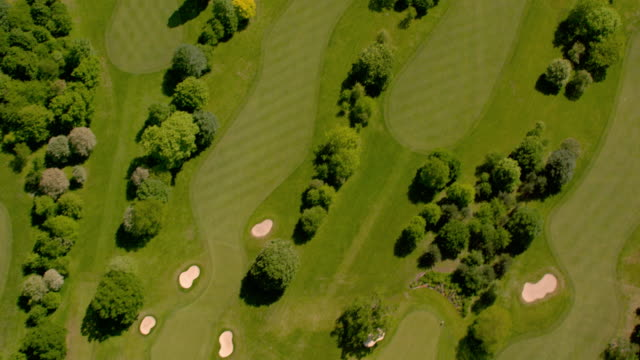 aerial view over a beautiful golf course in sunshine. 4k - golf stock videos & royalty-free footage