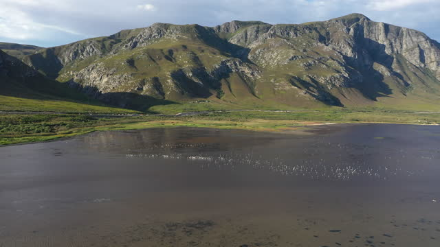 aerial view over a beautiful river with mountain backdrop - hermanus stock videos & royalty-free footage
