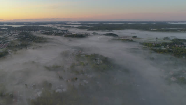 aerial view over a foggy rural landscape - high up stock videos & royalty-free footage