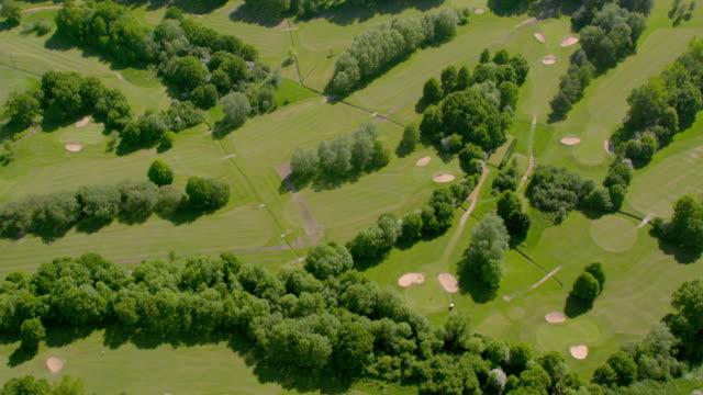 日差しの中でゴルフのコースを空撮。4 k - ゴルフ場点の映像素材/bロール