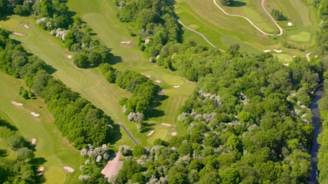 aerial view over a golf course in sunshine. 4k - country club stock videos & royalty-free footage