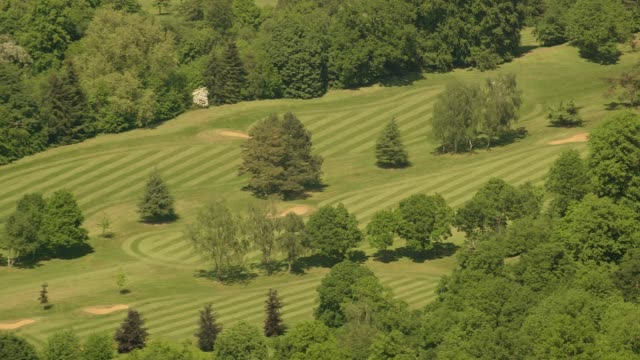 aerial view over a golf course in sunshine. 4k - clubhouse stock videos & royalty-free footage