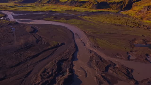 Aerial view over a richly and warmly-coloured landscape where meltwater from a glacier forms into a river, Iceland.