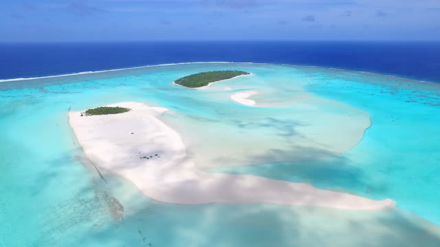 Aerial view over an island paradise, white sand beaches, turquoise lagoon and coral reef