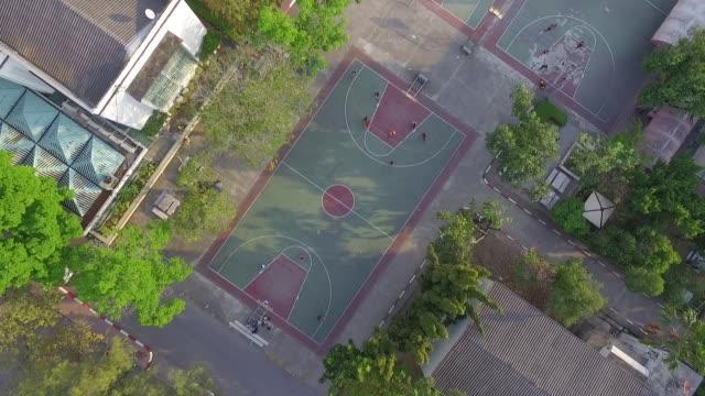 vídeos de stock, filmes e b-roll de aerial view over basket ball field - cesta