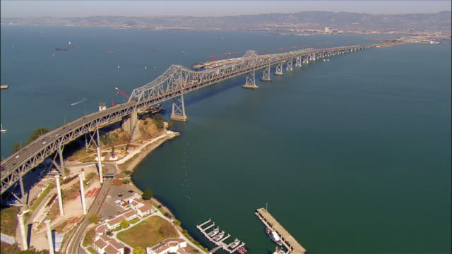 vídeos de stock e filmes b-roll de aerial view over bay bridge away from yerba buena island towards oakland / new bridge construction along side the east bay span / san francisco bay area, california - san francisco oakland bay bridge