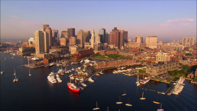 vídeos de stock, filmes e b-roll de aerial view over boats in the inner harbor w/ downtown skyline in background / over bridges crossing fort point channel / boston, massachusetts - boston massachusetts