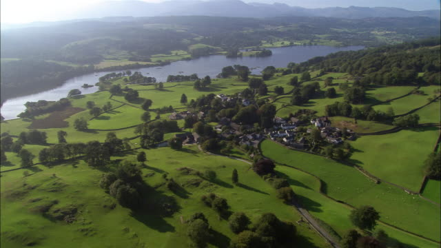 aerial view over cluster of houses in sawrey village (beatrix potter's village) in the lake district / windermere in background / cumbria, england - uk video stock e b–roll