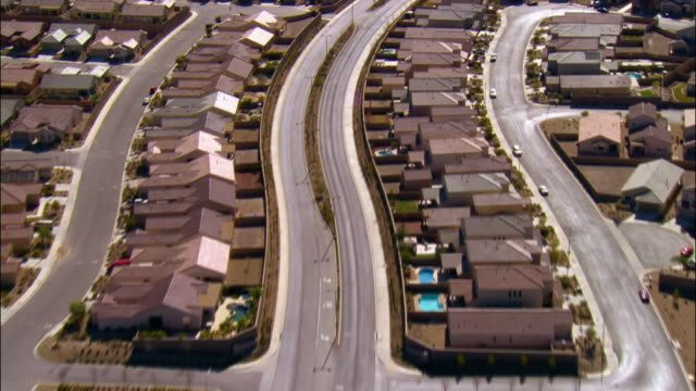 aerial view over curving road running through housing development / las vegas, nevada - residential district stock videos & royalty-free footage