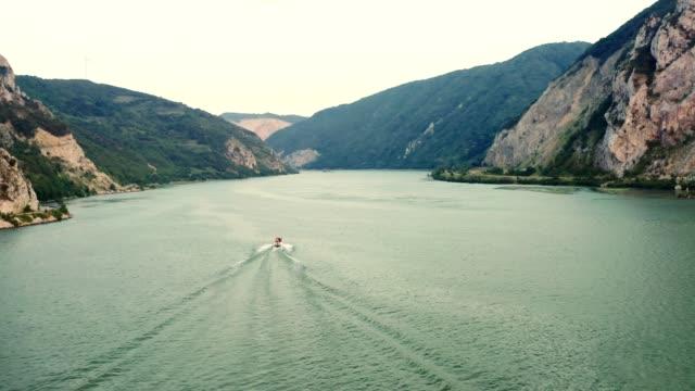 vidéos et rushes de vue aérienne au-dessus du fleuve de danube au coucher du soleil. drone volant au-dessus des bateaux sur l'eau. automne, soleil, destinations de voyage, tourisme, exploration, aventure, frontière, harmonie, tranquility, stock vidéo - river danube