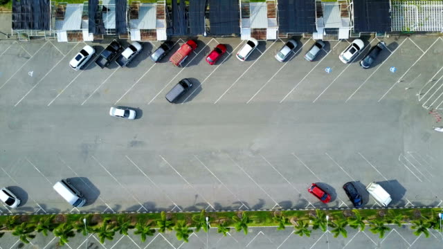 vídeos de stock e filmes b-roll de aerial view over departing and arrived car in parking lots with group of different color cars - top peça de roupa