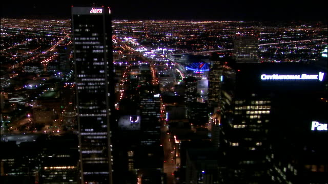 Aerial view over downtown skyscrapers and illuminated Staples Center at night / Los Angeles, California