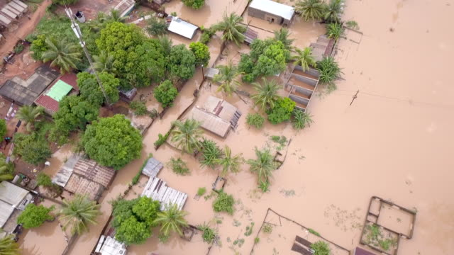 aerial view over flooded houses in village - emergencies and disasters stock videos & royalty-free footage