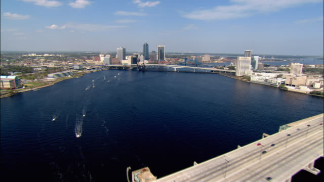 aerial view over fuller warren bridge, acosta bridge, and main street bridge, past skyscrapers of downtown and waterfront/ jacksonville, florida - jacksonville florida stock videos and b-roll footage