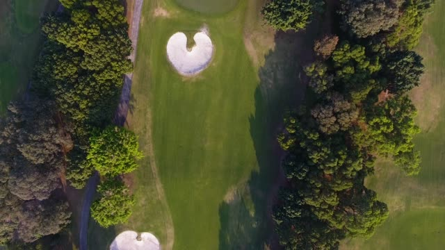 luftaufnahme über golf-feld in der stadt shenzhen. sonnenuntergang - golfplatz stock-videos und b-roll-filmmaterial