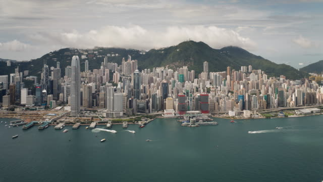 vídeos de stock, filmes e b-roll de  aerial view over hong kong island looking towards victoria peak showing the busy victoria harbour and financial district of central, hong kong, china, time-lapse - victoria peak