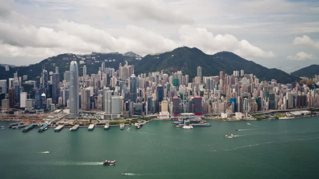 aerial view over hong kong island towards victoria peak showing the busy victoria harbour and financial district of central, hong kong, china, time-lapse - victoria harbour hong kong stock videos & royalty-free footage