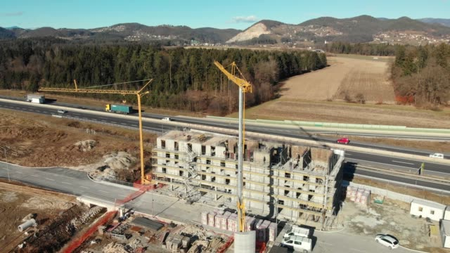 aerial view over hotel construction site - crane construction machinery stock videos & royalty-free footage