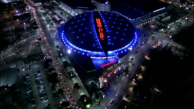 aerial view over illuminated staples center and downtown district at night / los angeles, california - staples centre stock videos & royalty-free footage