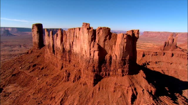 vidéos et rushes de aerial view over in monument valley near kayenta / past stagecoach and castle rock formations towards big indian rock / utah-arizona border - lieu touristique