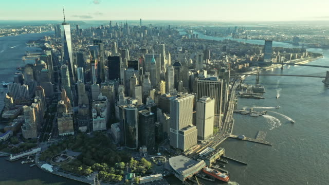 vídeos de stock, filmes e b-roll de aerial view over manhattan with rising sun between skyscrapers - new york city