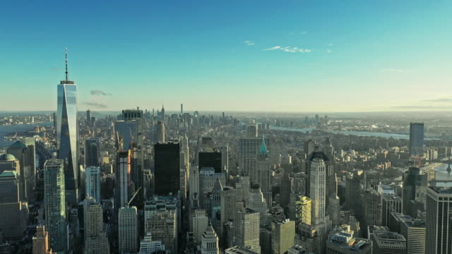 aerial view over manhattan with rising sun between skyscrapers - midtown manhattan stock videos & royalty-free footage