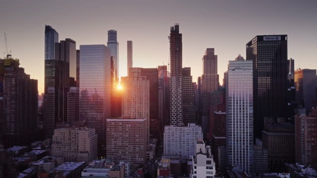 aerial view over manhattan with rising sun between skyscrapers - schwenk stock-videos und b-roll-filmmaterial