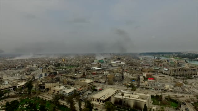Aerial view over Mosul with smoke visible and gunfire audible