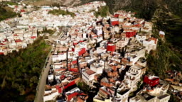 Aerial view over Moulay Idriss in a valley in Morocco, under the sun.