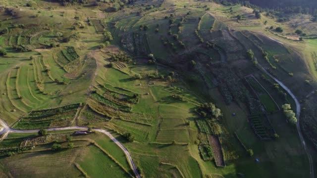 stockvideo's en b-roll-footage met luchtfoto over berg heuvels met groene velden bij zonsopgang met fel zonlicht-stockvideo - verwonderingsdrang
