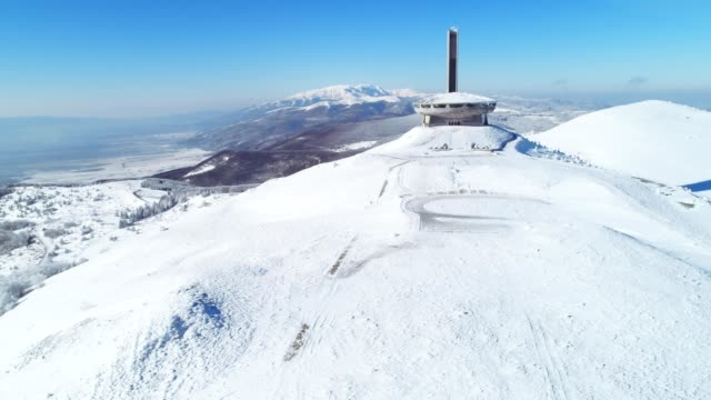 aerial view over mountain peak, architectural monument on top, wintertime, cultural and historical heritage, buzludja monument, ufo - monument stock videos & royalty-free footage