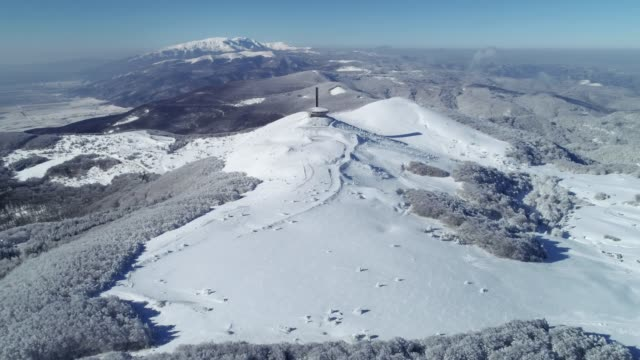 aerial view over mountain peak, architectural monument on top, wintertime, cultural and historical heritage, buzludja monument, ufo - communism stock videos and b-roll footage